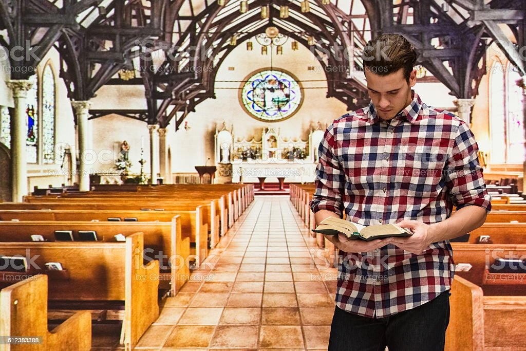 Man reading bible in church stock photo