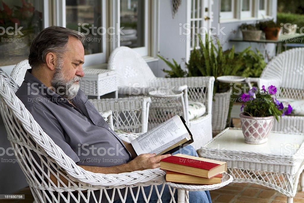 Man Reading Bible On Porch stock photo