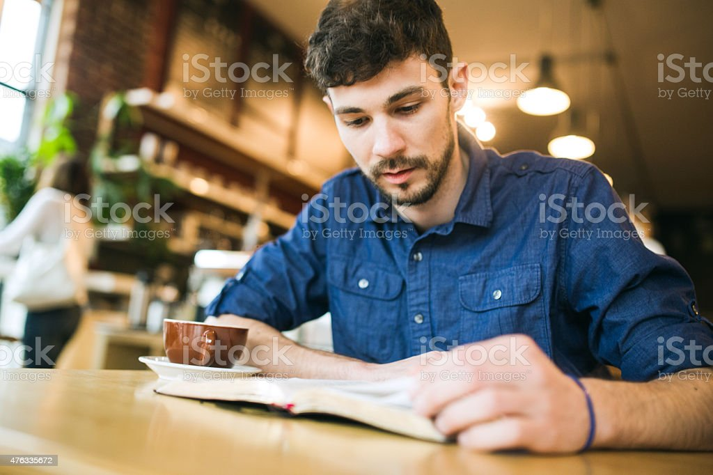 Man Reading Book in Coffee Shop stock photo