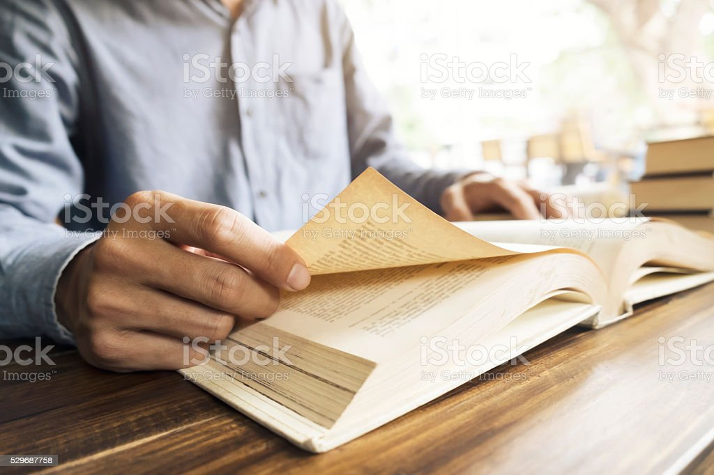 Man reading book in library or cafe. stock photo