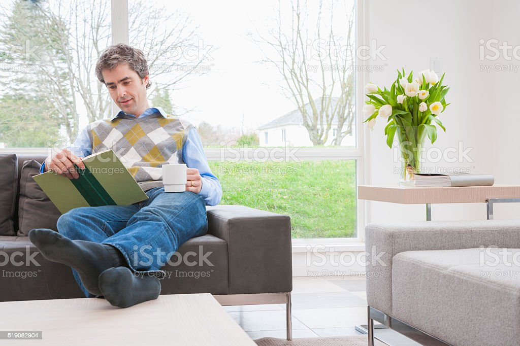 Man reading book on sofa with feet up stock photo