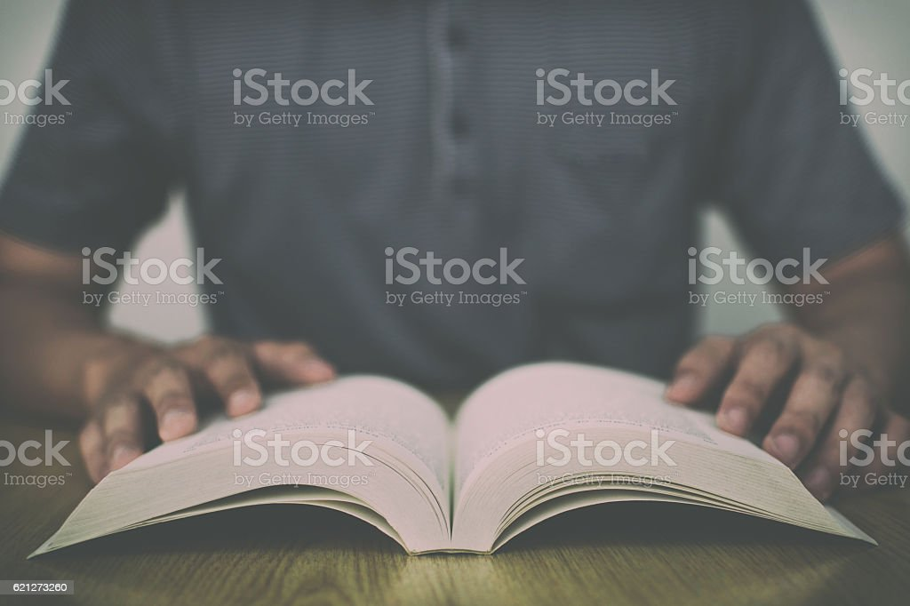 Man reading book on wooden table with vintage filter background stock photo