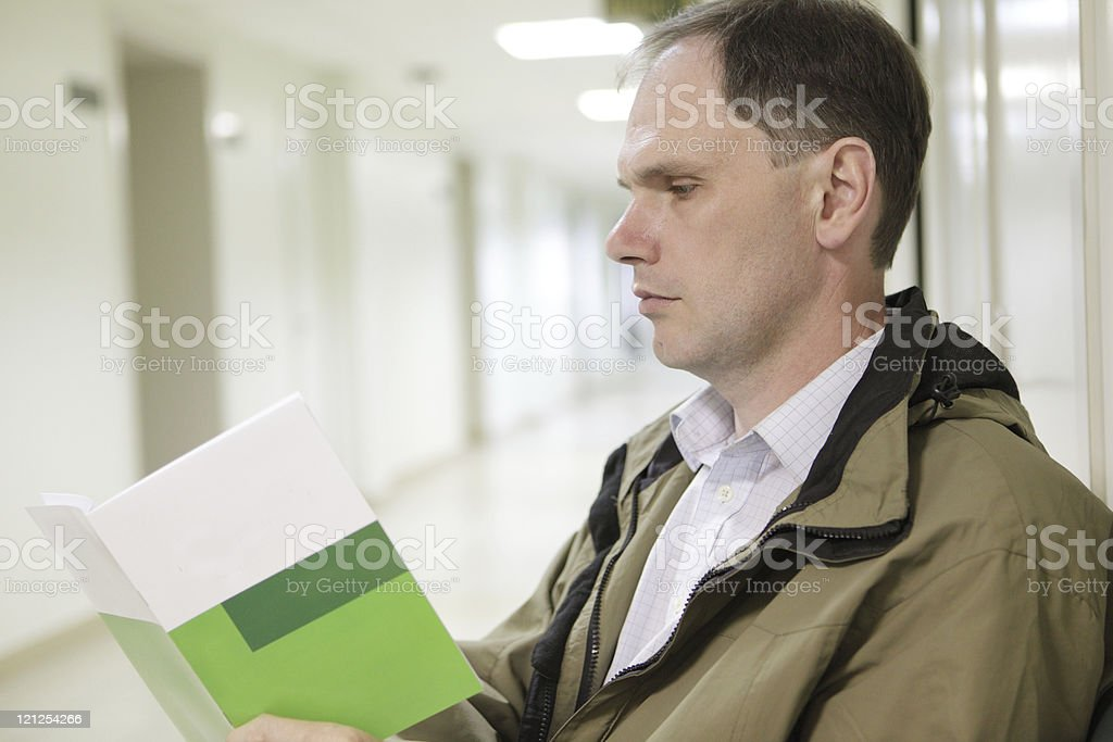 Man reading booklet in health clinic hallway royalty-free stock photo