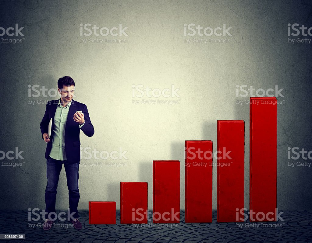 Man reading data on smartphone with growing up graph stock photo