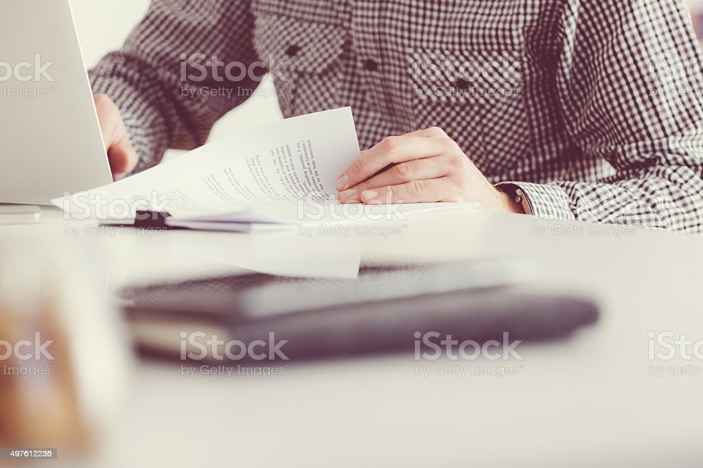 Man reading documents and using laptop, unrecognizable person stock photo