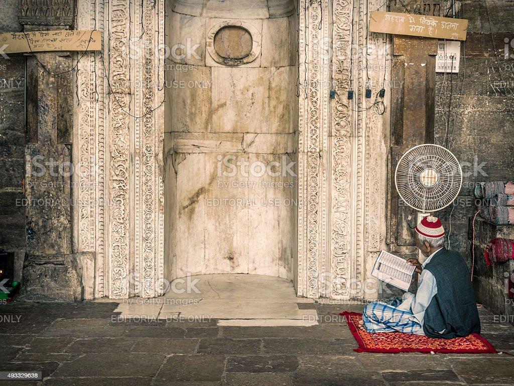 Man reading Koran in mosque in Ajmer India stock photo