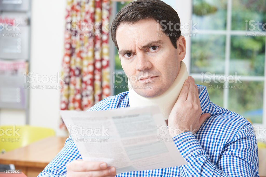 Man Reading Letter After Receiving Neck Injury stock photo