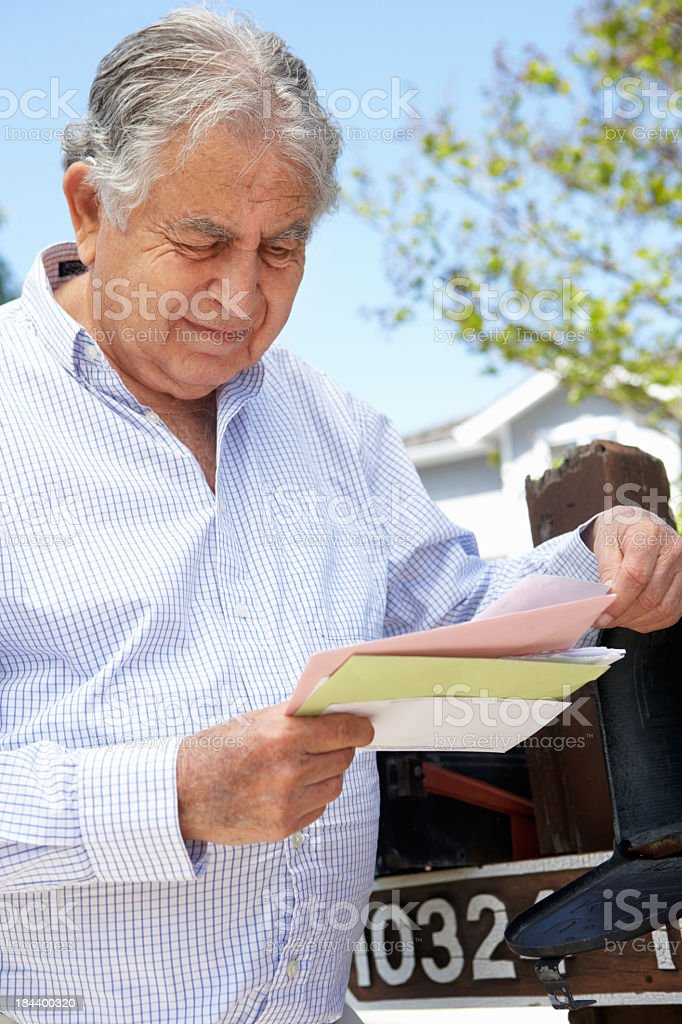 A man reading letters from his mailbox stock photo