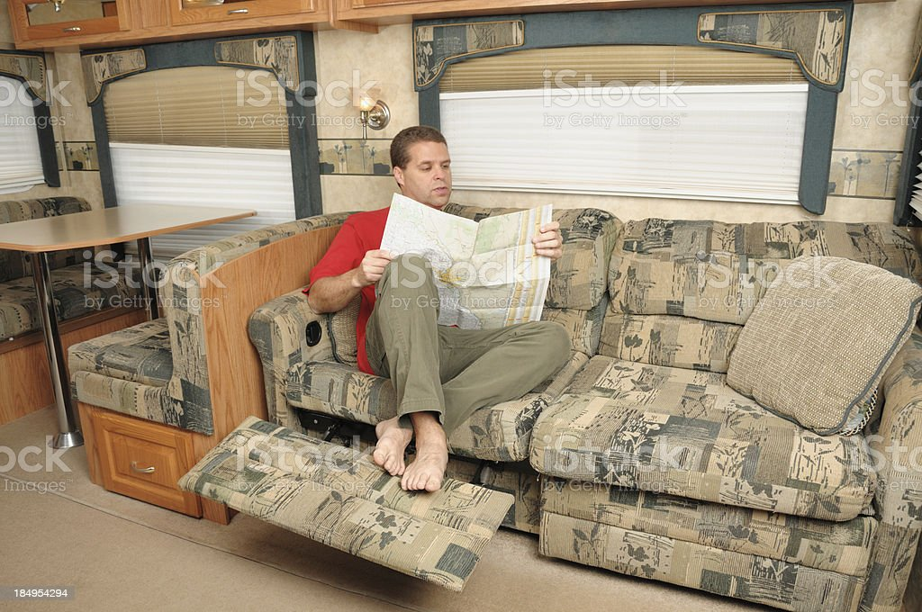 Man reading map in rv living room royalty-free stock photo