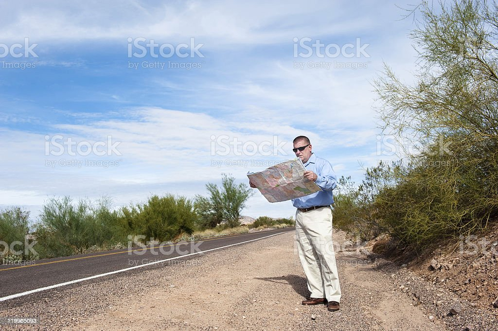 Man reading map on deserted road royalty-free stock photo
