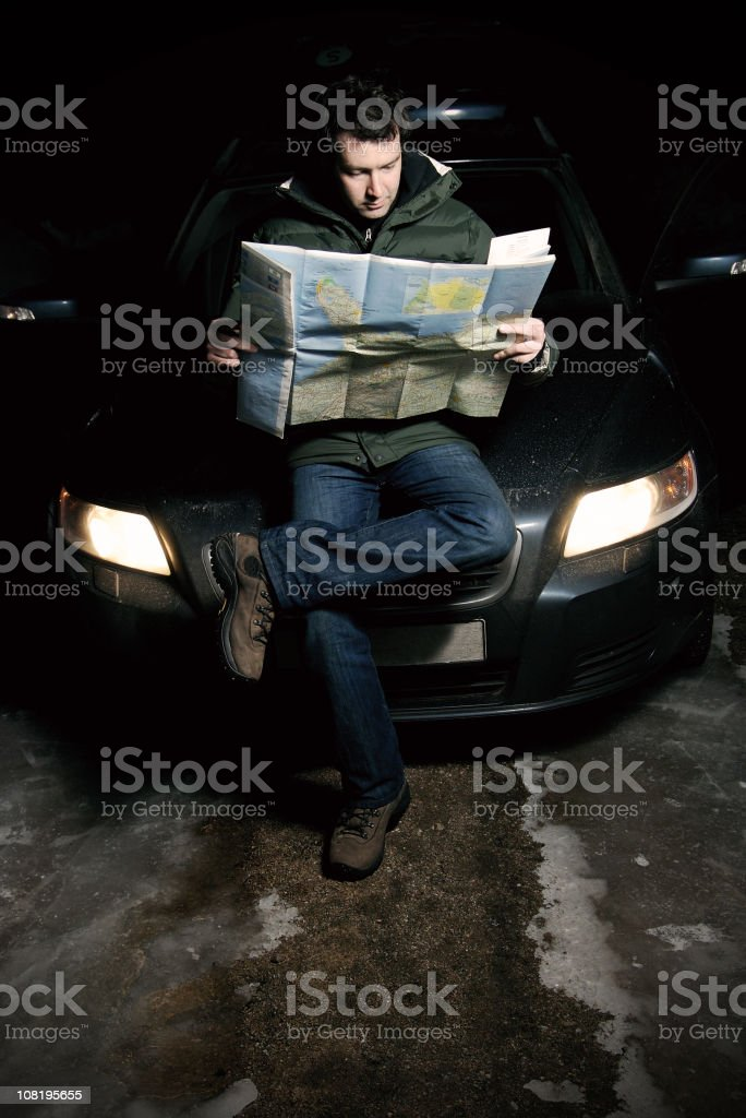 Man Reading Map on Hood of Car During Winter royalty-free stock photo