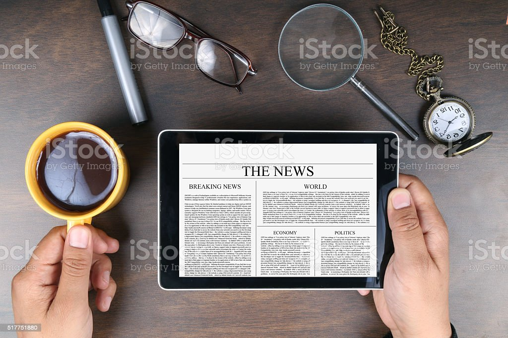 Man reading news on digital tablet stock photo