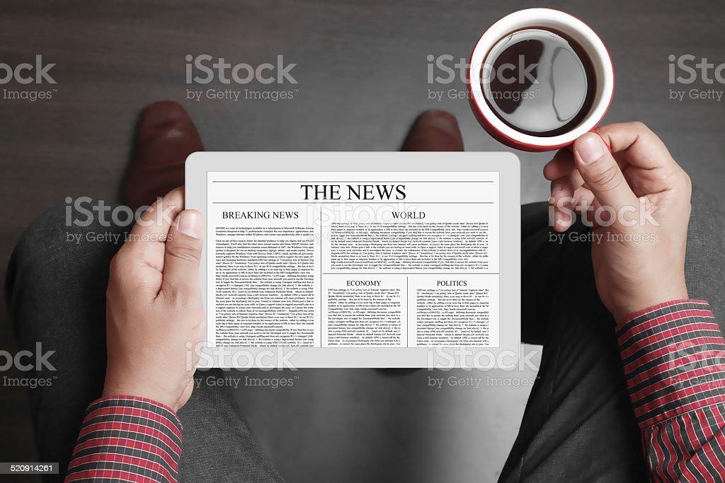 Man reading news on digital tablet stock photo