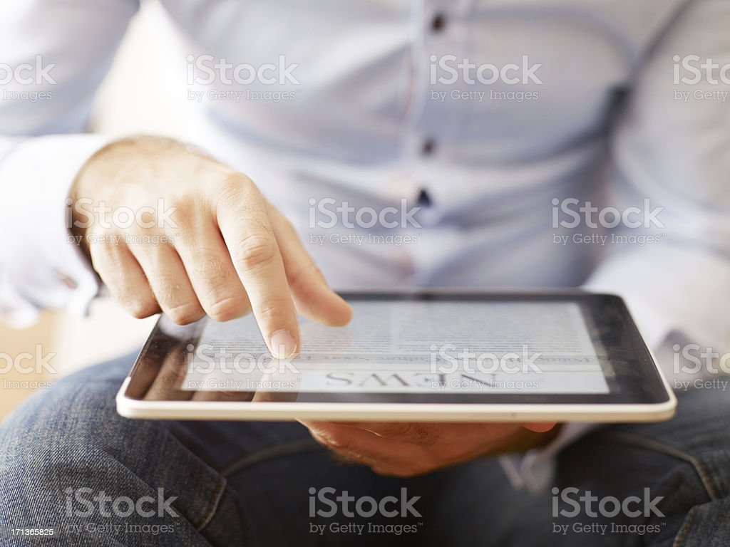 man reading news on the digital tablet stock photo