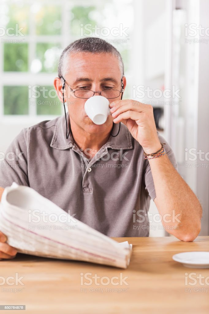 Man reading newspaper and drinking espresso stock photo