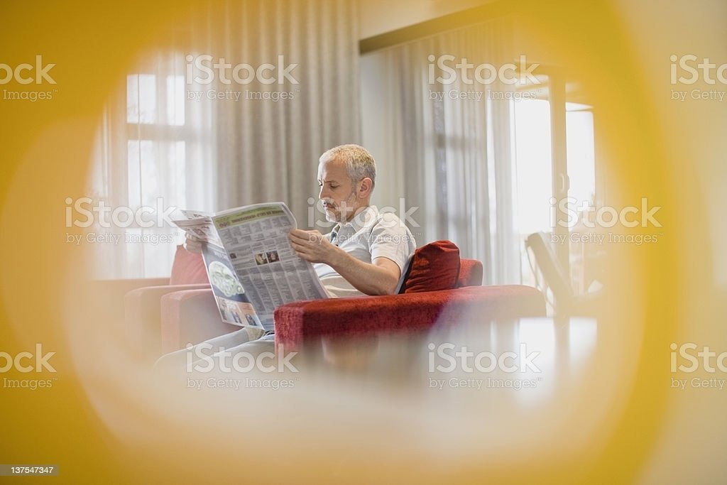 Man reading newspaper in armchair royalty-free stock photo