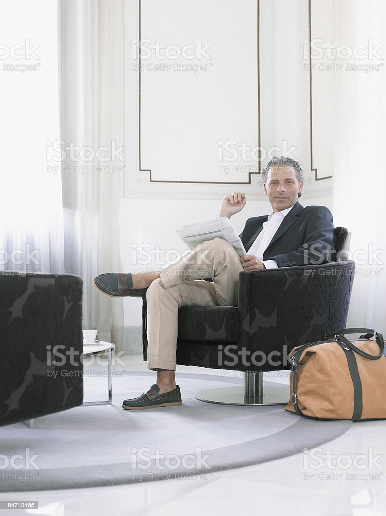 Man reading newspaper in modern hotel suite  stock photo