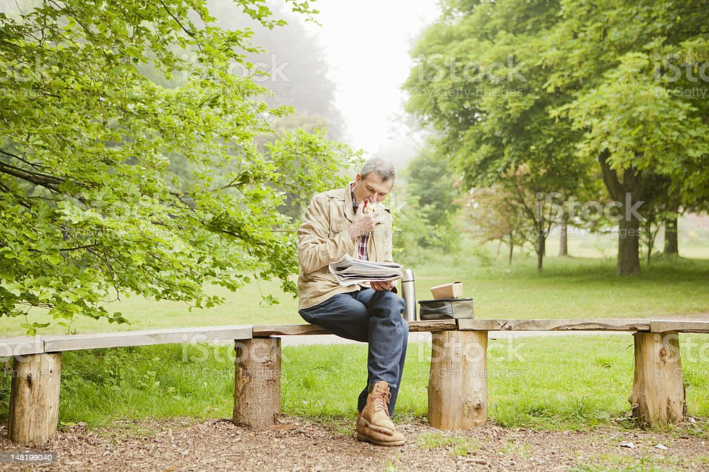 Man reading newspaper in park stock photo