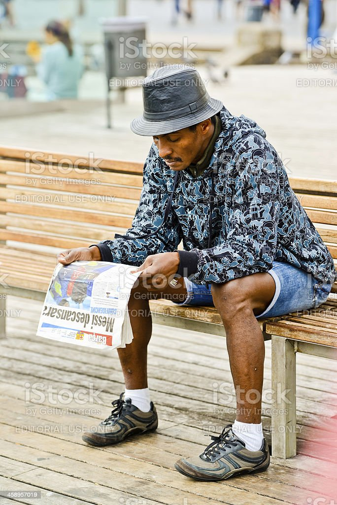 Man reading newspaper in Port Vell, Barcelona, Spain royalty-free stock photo