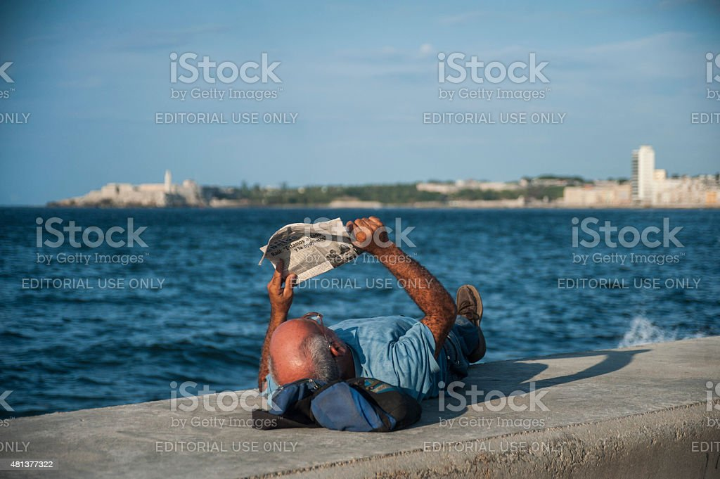 Man reading newspaper on Malecon stock photo