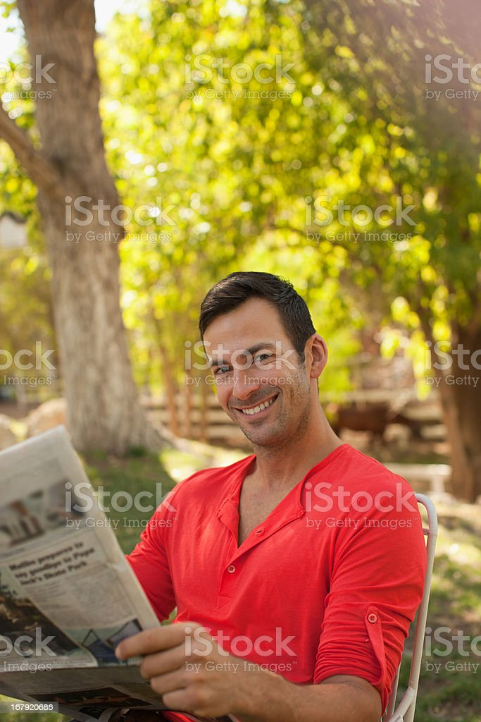Man reading newspaper outdoors stock photo