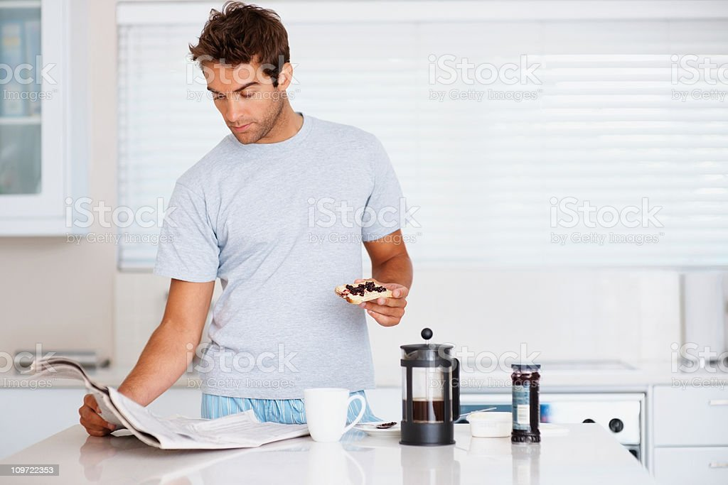 Man reading newspaper while eating breakfast royalty-free stock photo