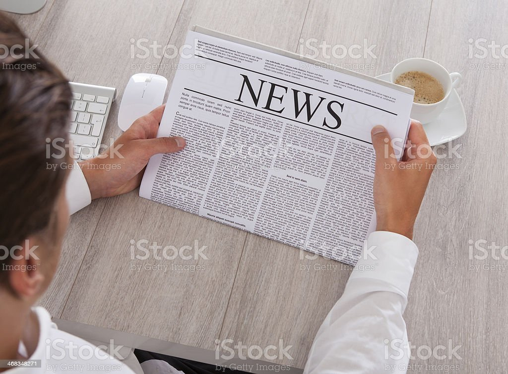 Man Reading Newspaper With Coffee On Desk stock photo