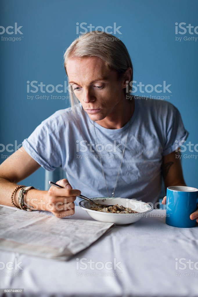 Man Reading The Morning Paper At Table stock photo