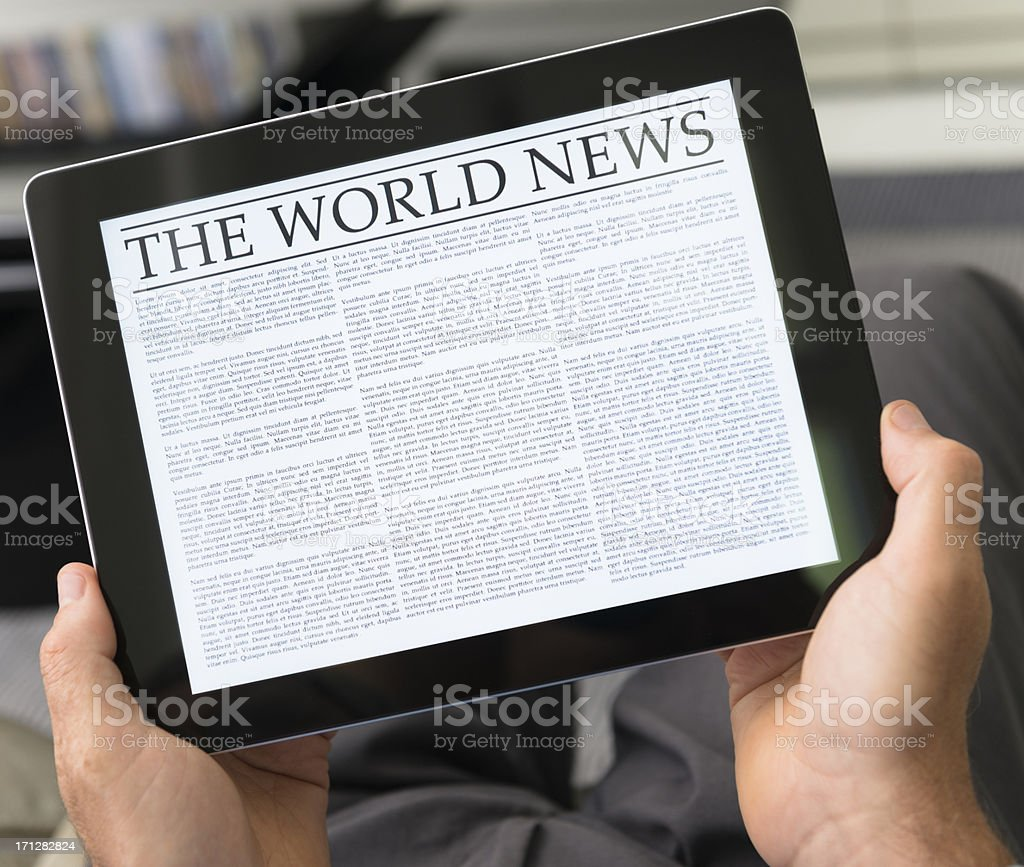 Man reading the newspaper on contemporary digital tablet at home royalty-free stock photo