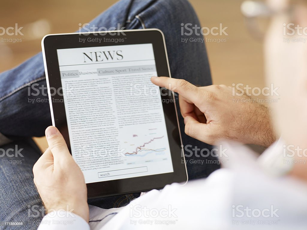 Man reading the newspaper on digital tablet stock photo