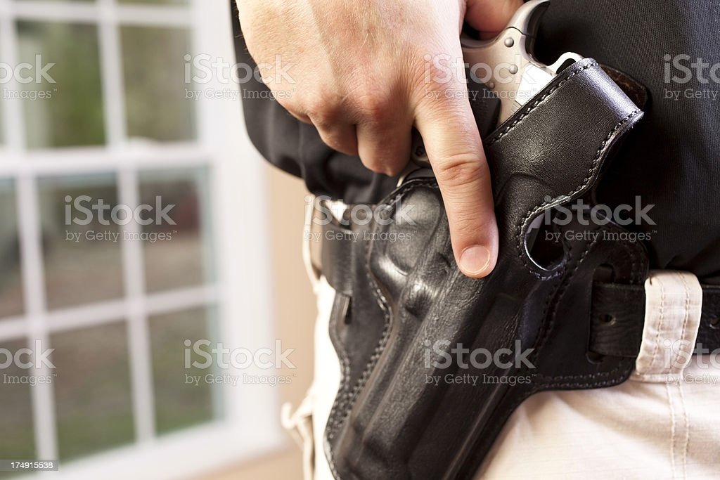 Man ready to draw gun weapon from leather holster stock photo