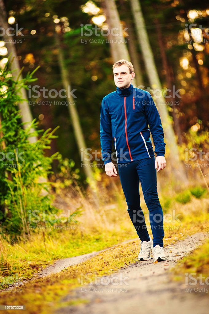 Man ready to run in a beautiful autumn landscape royalty-free stock photo