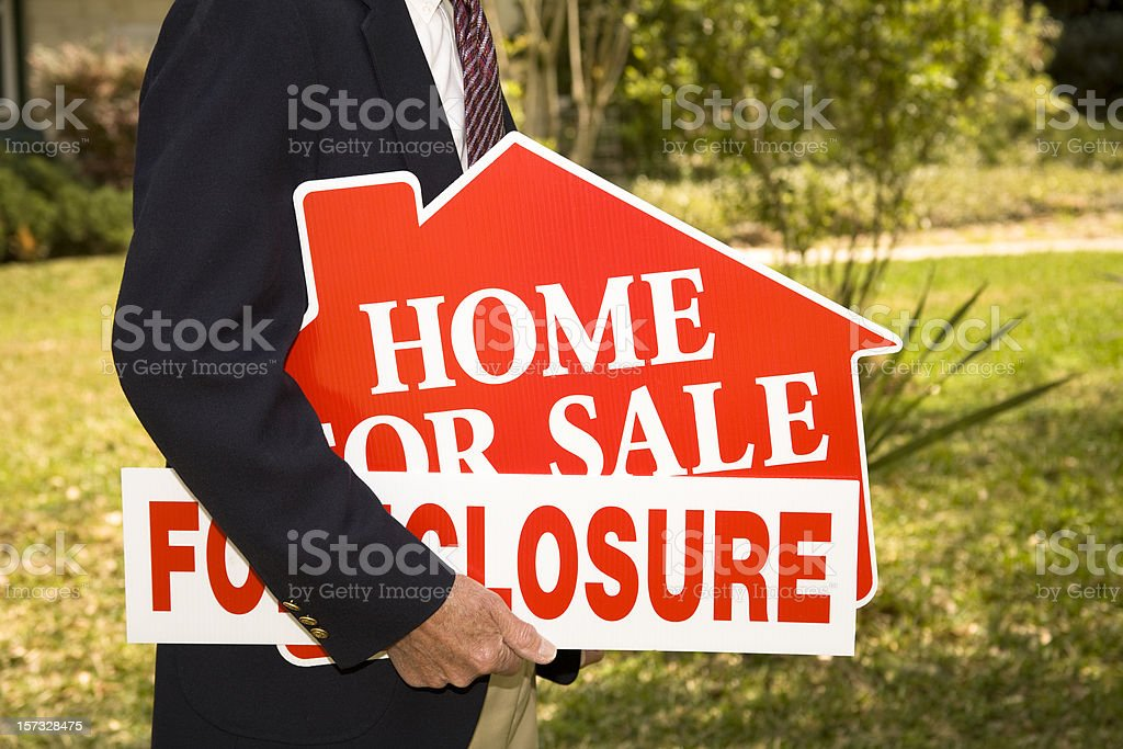 Man Realtor holds Foreclosure Real Estate Signs. Home. stock photo