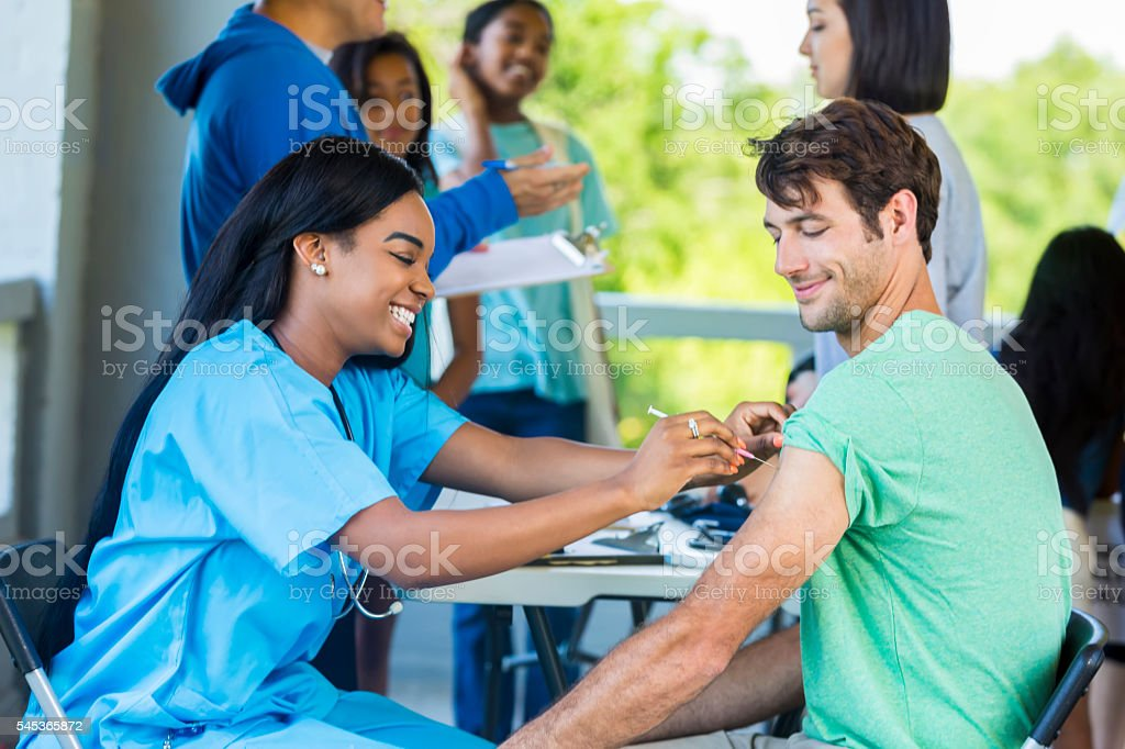 Man receives immunization at outdoor free clinic stock photo