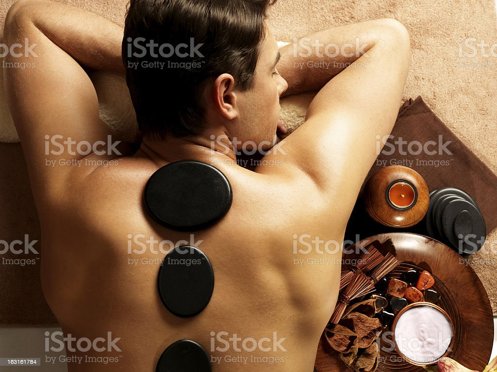 Man receiving a stone back massage in a spa stock photo