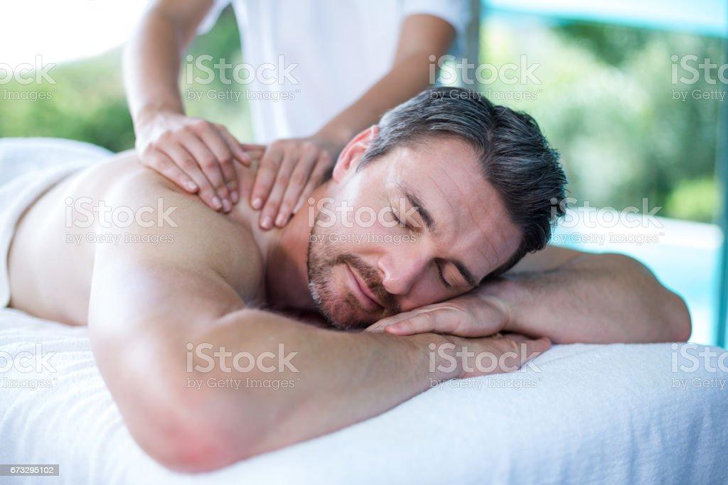Man receiving back massage from masseur stock photo