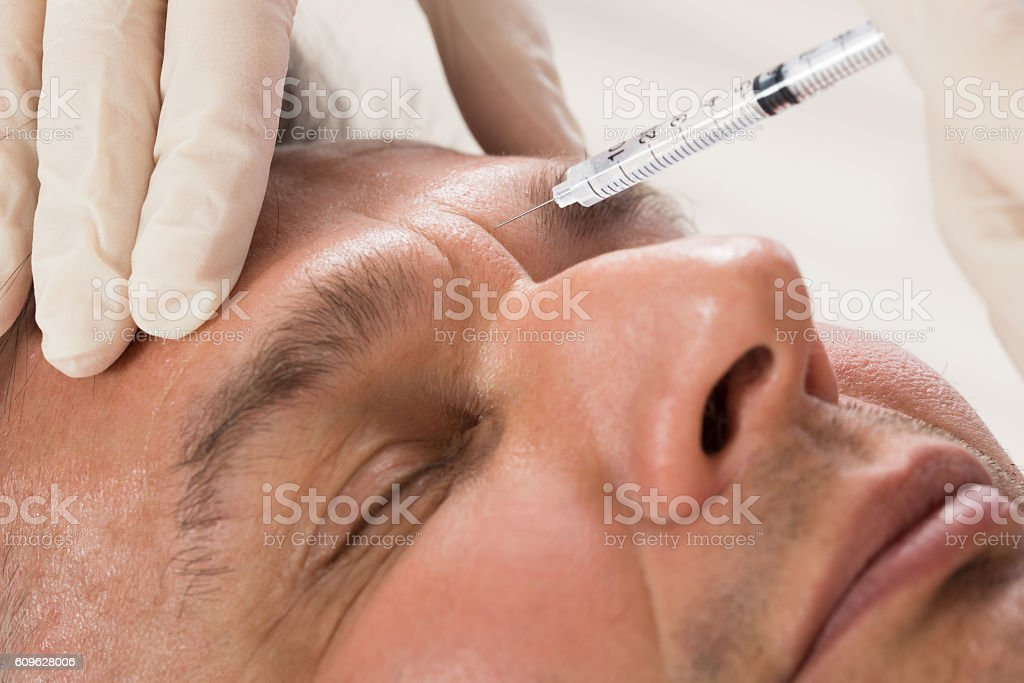 Man Receiving Cosmetic Injection With Syringe stock photo