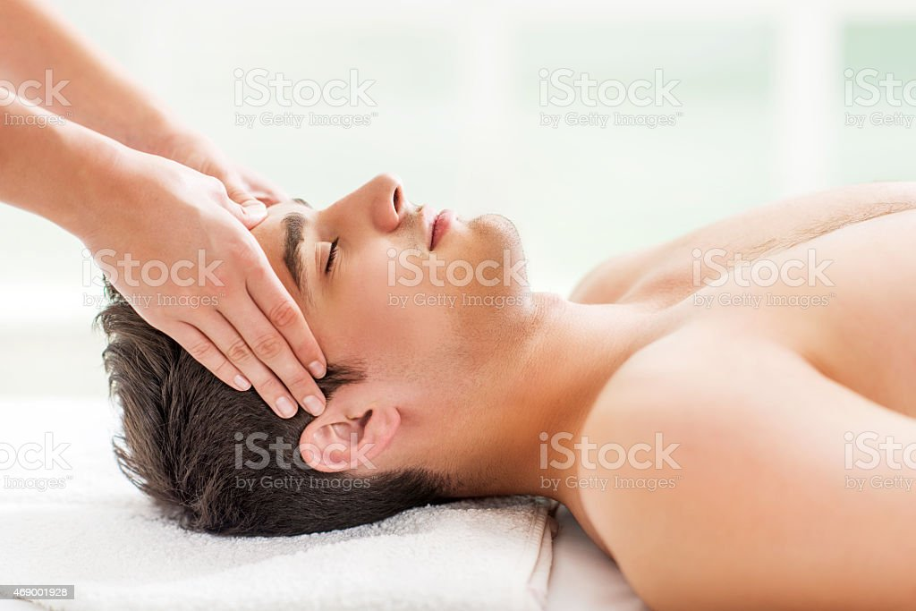 Man receiving head massage at spa. stock photo