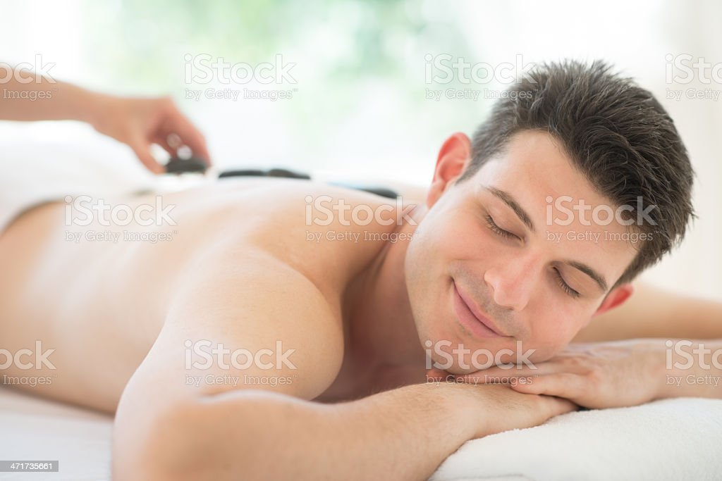Man Receiving Hot Stone Therapy At Spa royalty-free stock photo