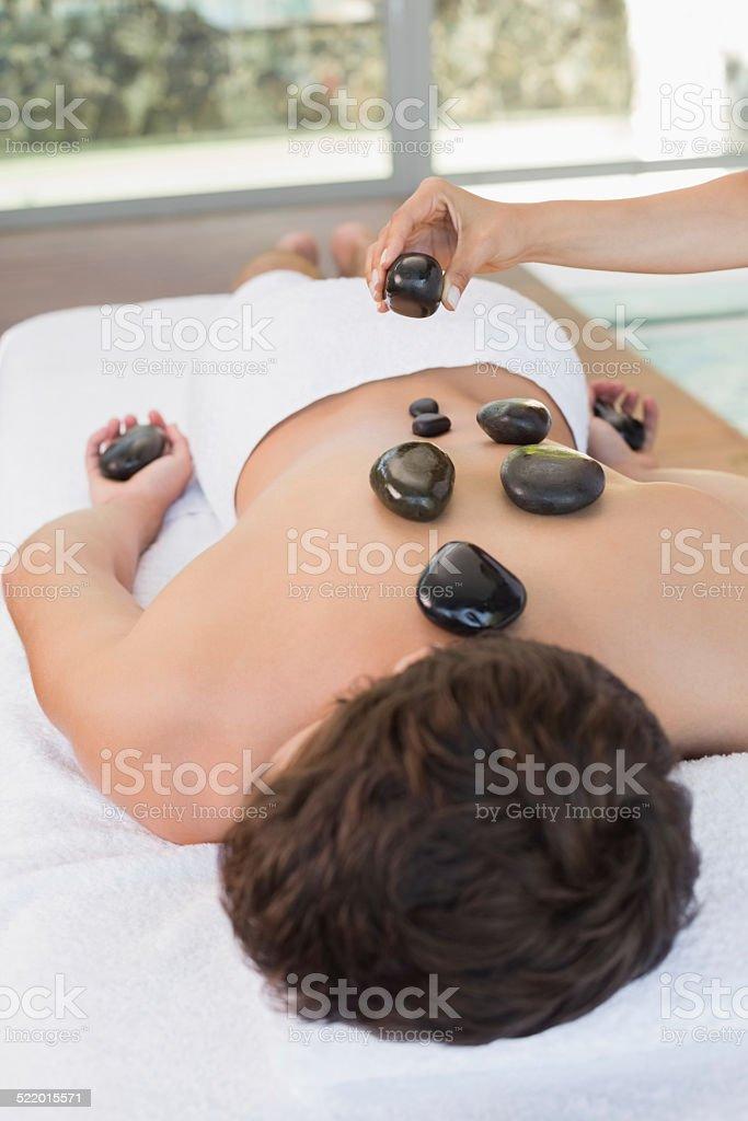 Man receiving stone massage at spa center stock photo