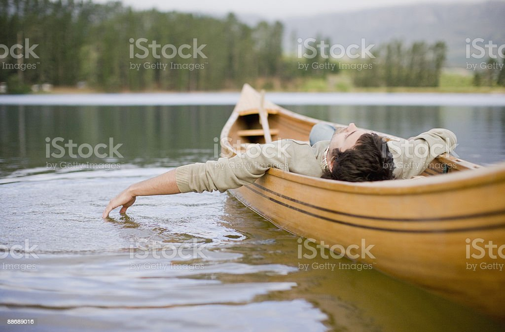 Man reclining in canoe on lake stock photo