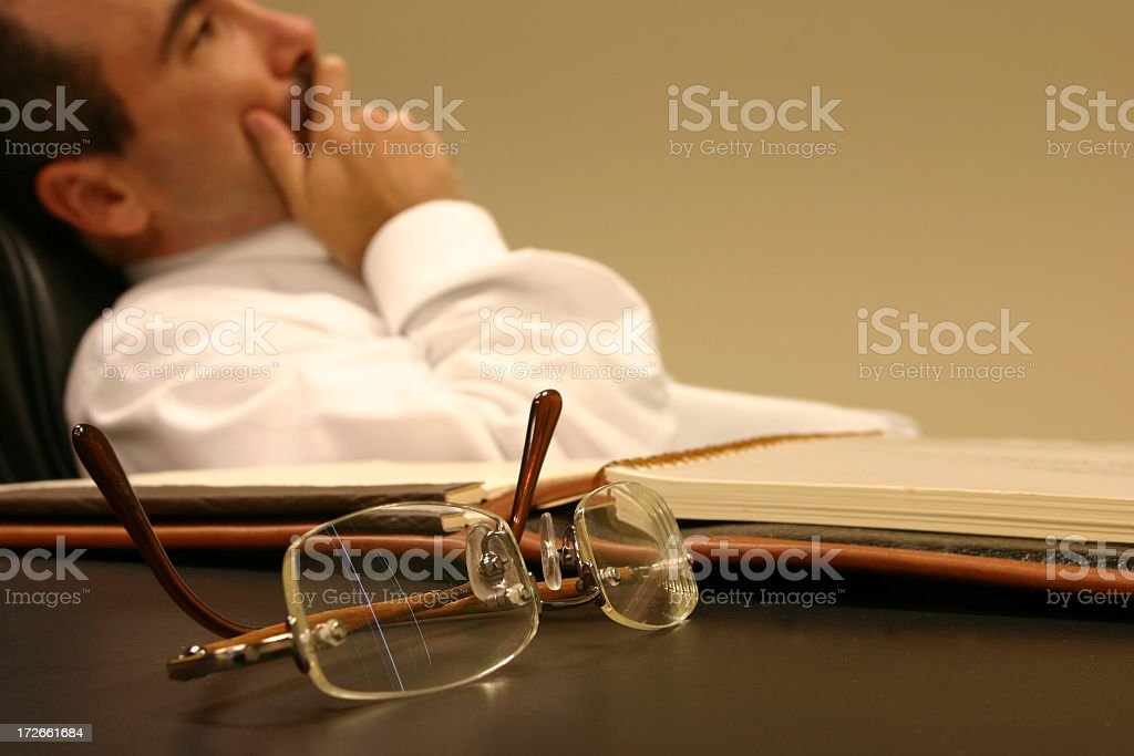 A man reclining in his office chair in deep pensive thought royalty-free stock photo