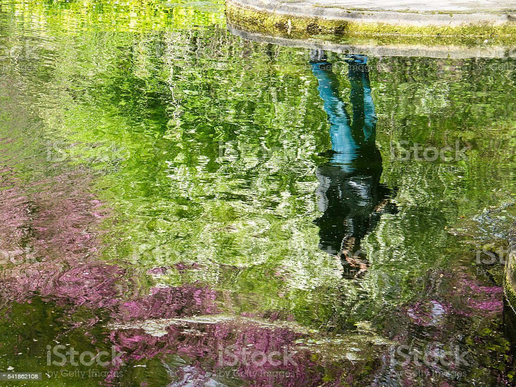 Man reflected in the water of the lake stock photo