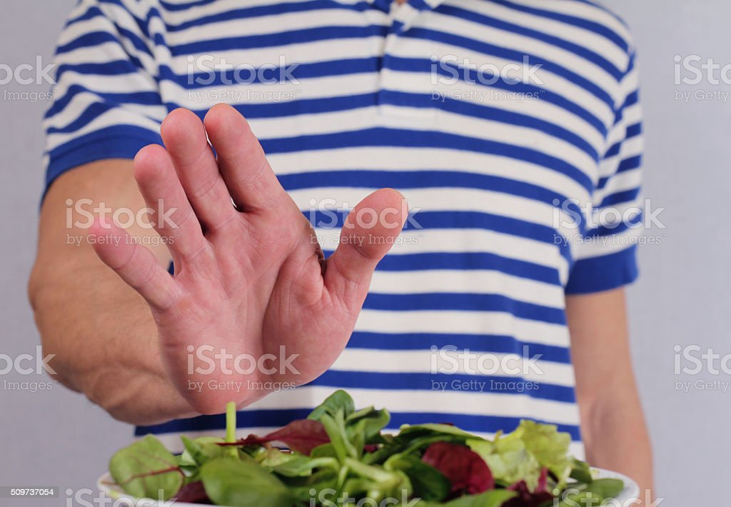 Man refuses to eat salad vegetables stock photo