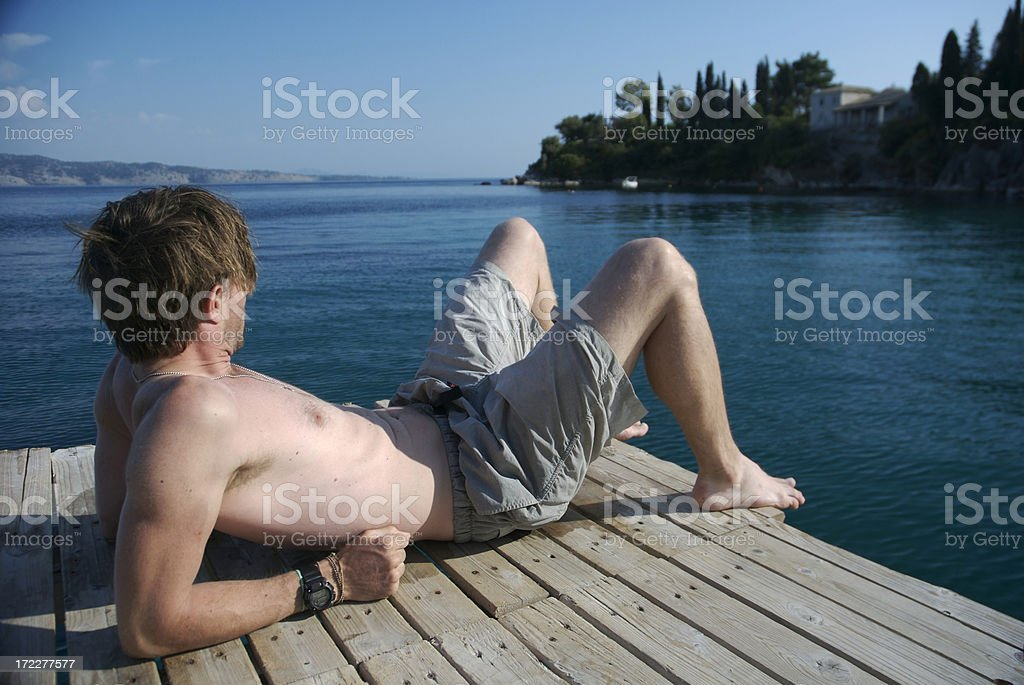 Man Relaxes on Wood Dock Over Calm Waters royalty-free stock photo