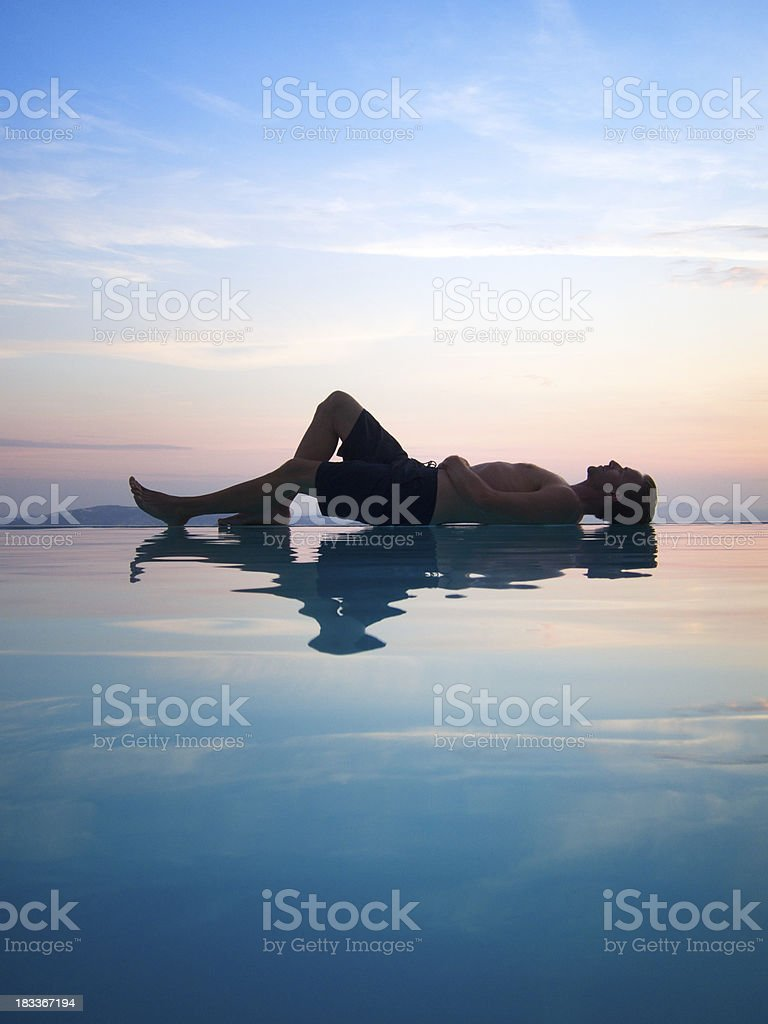 Man Relaxes Reflecting on Sunset Infinity Swimming Pool royalty-free stock photo