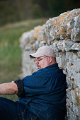 Man Relaxing Against Stone Wall