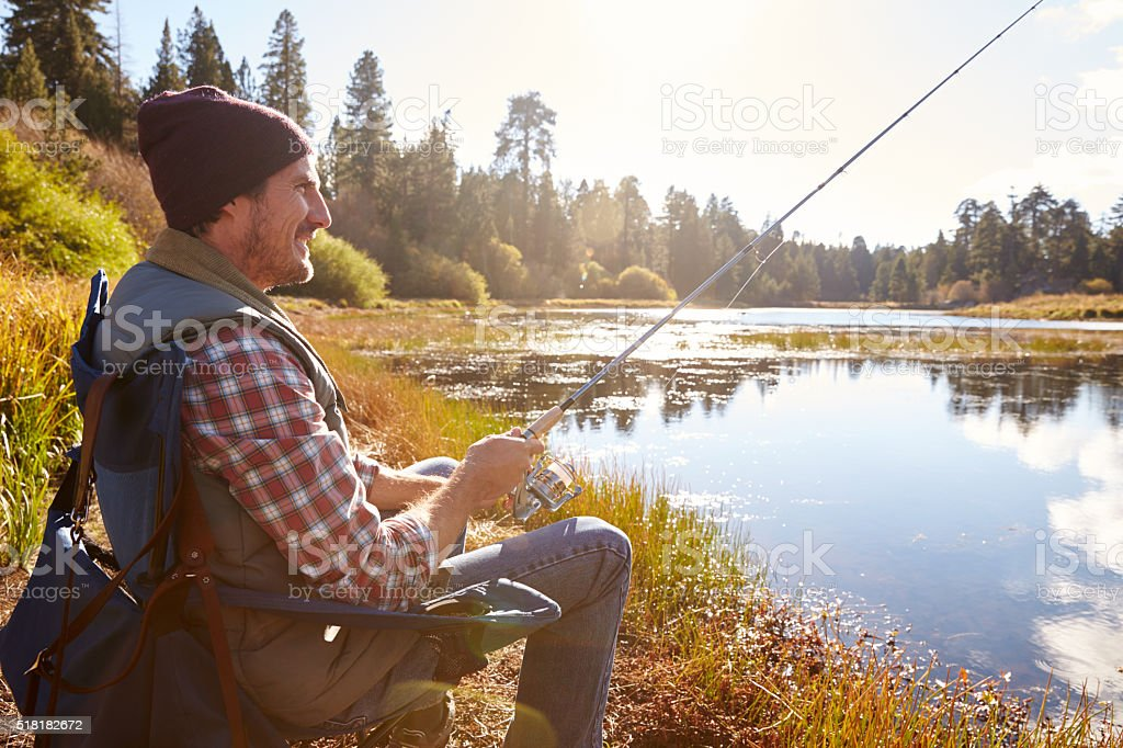 Man relaxing and fishing by lakeside, California, USA stock photo