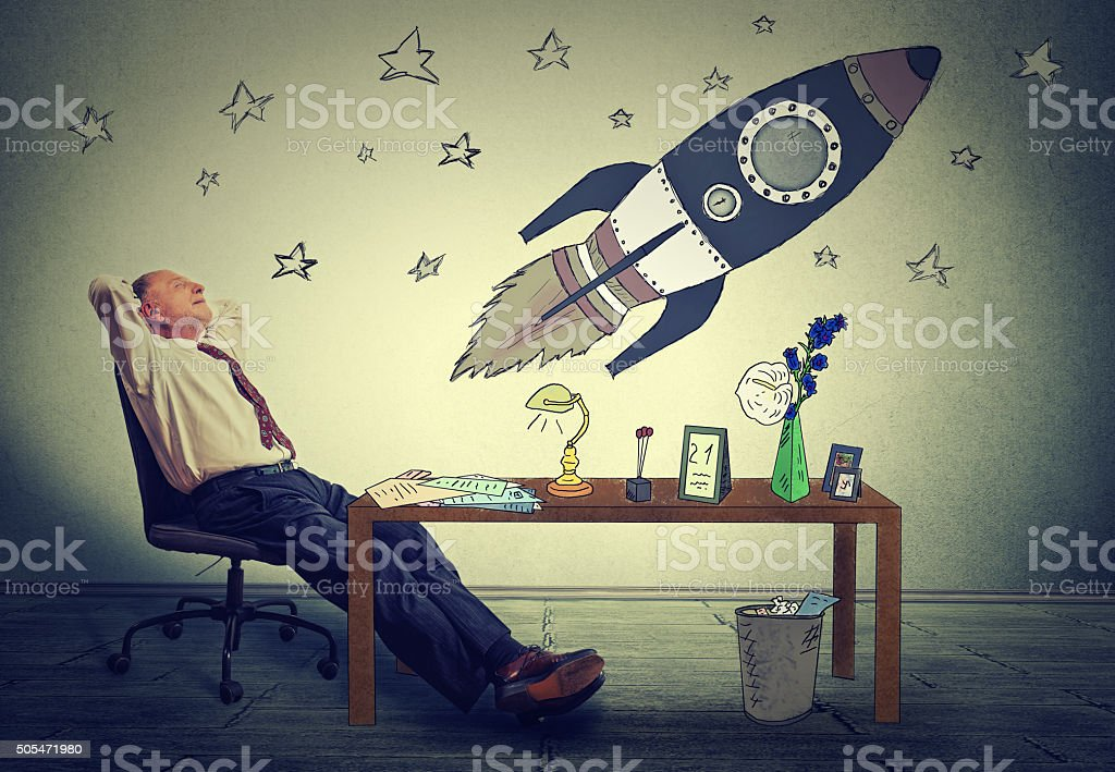 Man relaxing at desk in office daydreaming of space tourism stock photo