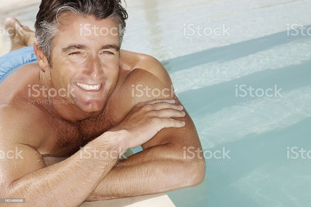 Man relaxing besides a pool on vacation royalty-free stock photo